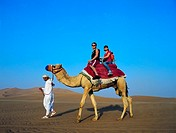 Western couple riding a camel in the desert of the UAE