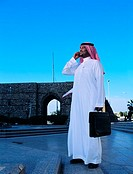 Saudi man using mobile phone near ancient gate of Old Town in Jeddah, Saudi Arabia