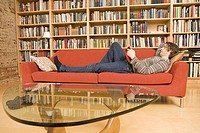 Side profile of a young man lying on a couch and reading a book