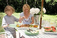 Young woman sitting at a table with her son choosing food from a tray
