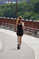 Rear view of a young woman jogging on a road