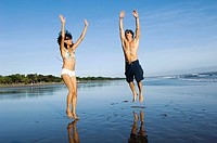 young couple jumping on the beach