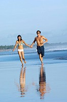young couple running on the beach