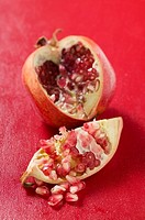 Pomegranate, cut open, on red background