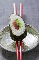 A maki sushi with tuna and cucumber on chopsticks