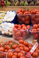 Tomatoes and mushrooms in plastic punnets at a market