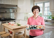 Senior Asian woman holding tray of sushi
