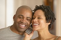 African couple listening to same cell phone and smiling