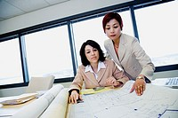 Two businesswomen looking at blueprints