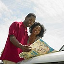 African couple looking at map on hood of car