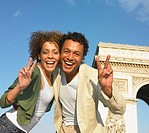 Couple making peace signs next to stone arch in Paris