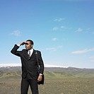 Businessman shading eyes in deserted rural area