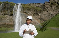 Man with hard hat and clipboard in front of waterfall