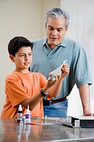Hispanic father and son building model airplane
