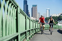 Couple riding bicycles on urban bridge