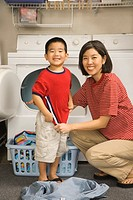 Asian mother and son with clean laundry next to dryer