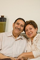 Senior Hispanic couple hugging and smiling indoors