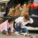 Brother and sister with dropped groceries in driveway