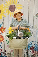 Senior woman holding gardening basket with flowers and dog
