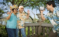 Young man using video camera to film senior couple waving