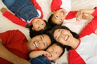 High angle view of Asian family laying on bed