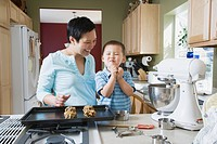 Asian mother and young son making cookies