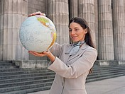 Businesswoman holding globe in front of building