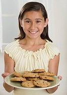 Hispanic girl holding plate of cookies