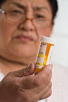 Senior Hispanic woman looking at medication bottle