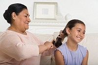 Hispanic grandmother brushing granddaughter´s hair