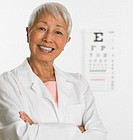 Senior Asian female doctor with eye chart in background