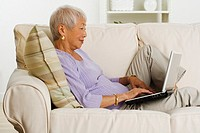 Senior Asian woman using laptop on sofa