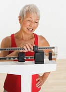 Senior Asian woman adjusting scale