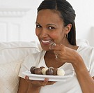 African woman eating chocolate truffles