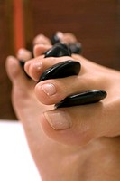 Woman receiving hot stone massage on feet, close-up