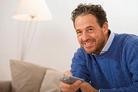 Man sitting on sofa, holding remote control