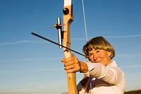 Senior adult woman using bow and arrow