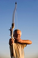 Senior adult man using bow and arrow