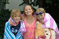 Three friends playing in a backyard pool