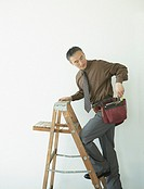 Asian businessman with toolbelt climbing up ladder