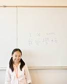 Young girl smiling in front of whiteboard in classroom