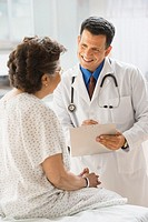 Hispanic male doctor talking to patient