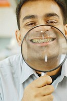 Indian man holding up magnifying glass to his teeth with braces