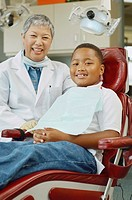 Senior Asian female dentist and African boy in dentist's chair