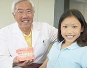 Senior Asian male dentist showing model of teeth to young patient