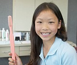 Asian girl holding large toothbrush at dentist's office