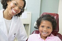African female dentist examining young female patient