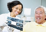 African female dentist showing x-rays to senior male patient