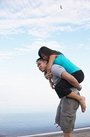 Asian man giving girlfriend piggy back ride at beach