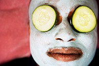 African man with facial mask and cucumber slices on eyes